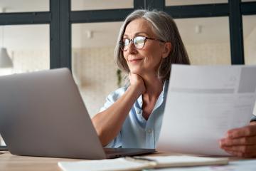 Vrouw zit achter een computer en houdt bladen papier vast